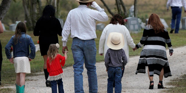A mourner arrives with his children for the burial of Richard and Therese Rodriguez after the husband and wife were killed in the shooting at First Baptist Church of Sutherland Springs in Texas, Nov. 11, 2017.