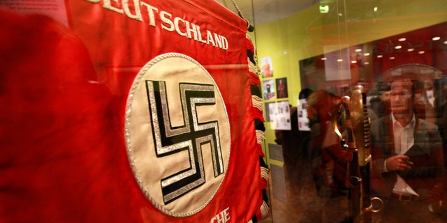 """File photo - A flag with the Nazi swastika is pictured at the media preview of """"Hilter und die Deutsche Volksgemeinschaft und Verbrechen"""" (Hitler and the German Nation and Crime) at the Deutsche Historisches Museum (German Historical Museum) in Berlin Oct. 13, 2010. The words on the flag read """"Germany wake up"""". (REUTERS/Fabrizio Bensch)"""