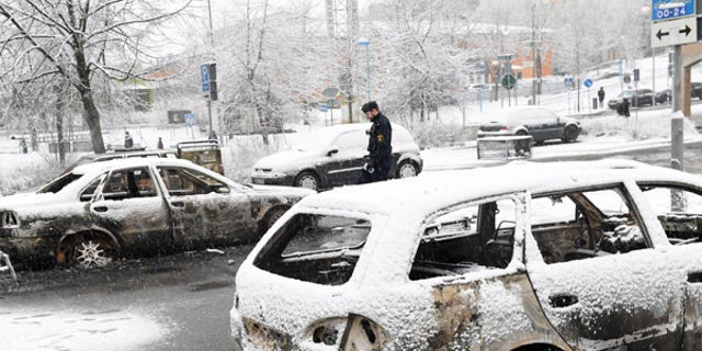 A policeman investigates a burned car in the suburb of Rinkeby on Monday.