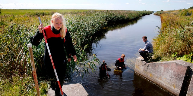 Police and other authorities search a waterway for body remains related to the ongoing Kim Wall murder investigation at the west coast of Amager close to Copenhagen, Denmark on Aug. 23, 2017.