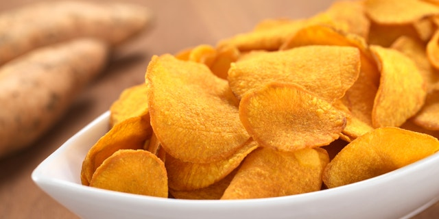 Crispy Peruvian sweet potato chips in white ceramic bowl with sweet potatoes in the back (Selective Focus, Focus one third into the sweet potato chips)