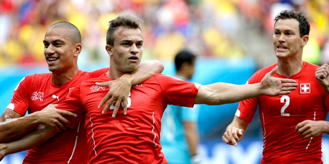 June 25, 2014: Switzerland's Xherdan Shaqiri, center, celebrates with teammate  Goekhan Inler, left, and Stephan Lichtsteiner (2) after scoring during the group E World Cup soccer match between Honduras and Switzerland at the Arena da Amazonia in Manaus, Brazil.
