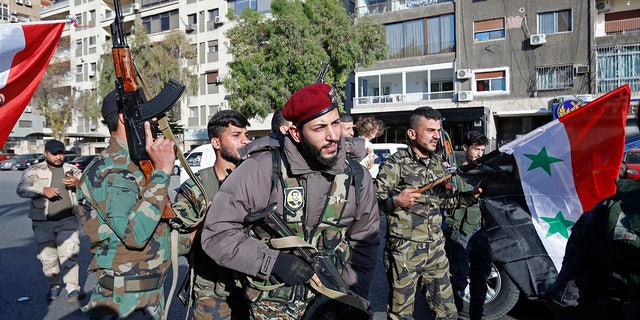 Syrian soldiers wave weapons and national flags in Damascus the morning after the U.S.-led airstrikes.