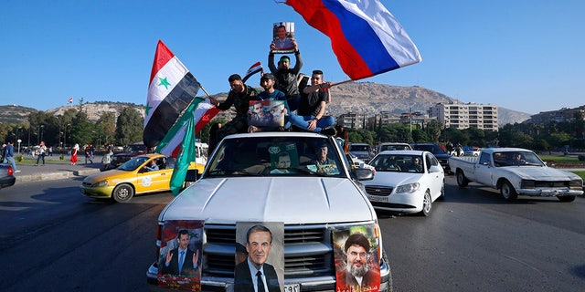 A convoy of cars with pro-government supporters in Damascus.