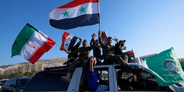 Syrian government supporters wave Syrian, Iranian and Russian flags as they chant slogans against U.S. President Trump.