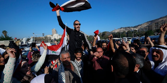 Syrian government supporters took to the streets of Damascus, waving flags and chanting slogans against U.S. President Trump during demonstrations.