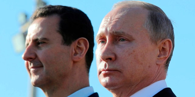 Russian President Vladimir Putin, right, and Syrian President Bashar Assad watching troops march at the Hemeimeem air base in Syria.