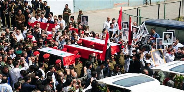 April 26: In this photo released by the Syrian official news agency SANA, Syrian military police carry coffins as they prepare to send the bodies of fifteen killed soldiers and security force members to their hometowns for burial, at a military hospital in Damascus, Syria. The agency did not report the circumstances of their deaths but they are believed to have been victims of the ongoing civil unrest against the government. (AP/SANA)