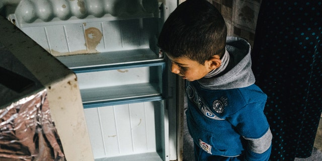 Jan. 24, 2016: A Syria refugee boy opens an empty fridge inside his family tent in Kawergosk refugee camp in northern Iraq.