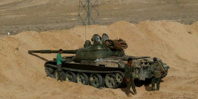 March 24, 2016: In this photo released by the Syrian official news agency SANA, Syrian government soldiers stand next to their tank, near the entrance of the town of Palmyra, in central Syria.