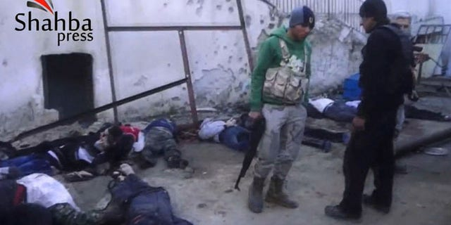 This image made from citizen journalist video posted by the Shahba Press on Wednesday, Jan. 8, 2014, which has been verified and is consistent with other AP reporting, shows rebel fighters standing next to dead bodies after they ousted Islamic State of Iraq and the Levant (ISIL) from their headquarters in a hospital in the Syrian city of Aleppo. Activists said the people were killed by fighters from the Al Qaeda affiliate, which is trying to build Islamic rule across Syria.