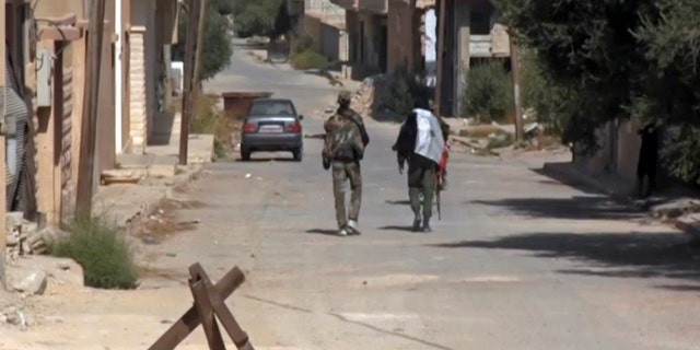 This Saturday, Oct 21, 2017 frame grab from video, shows two Syrian soldiers walking in the street of Qaryatayn, a town in central Syria which was recaptured from Islamic State group militants on Saturday.