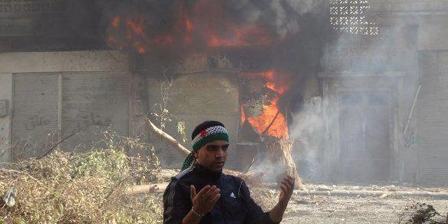Feb. 12, 2012: In this citizen journalism image provide by the Local Coordination Committees in Syria, an anti-Syrian regime man reacts in front of flames which rise from a burning shop damaged by Syrian government forces shelling, in Baba Amr neighborhood in Homs province, central Syria.