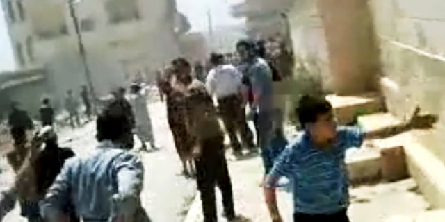 In this image made from amateur video released by the Shaam News Network and accessed Tuesday, May 15, 2012, purports to show Syrians running from gun shots in Khan Sheikhoun, Idlib, Syria.
