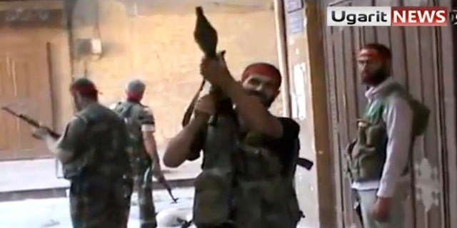 Sept. 28, 2012: In this image taken from video obtained from Ugarit news, which has been authenticated based on its contents and other AP reporting, Syrian rebels gather as they engage government forces in Aleppo, Syria.
