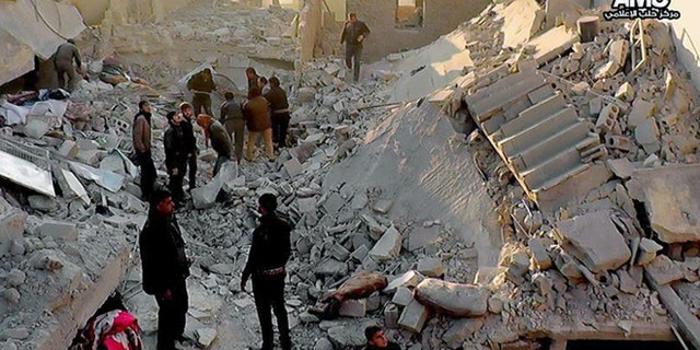 Jan. 6, 2014: In this citizen journalism image provided by Aleppo Media Center, AMC, Syrians inspect the rubble of destroyed buildings following a Syrian government airstrike in Aleppo.