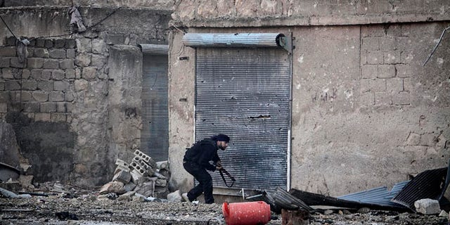 Dec. 5, 2012: A Free Syrian Army fighter runs for cover during heavy clashes with government forces, not pictured, in Aleppo, Syria.