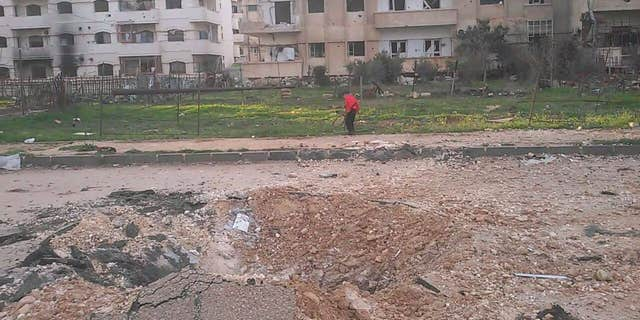 Child plays in remains of a park in Al Waer, Homs in Syria