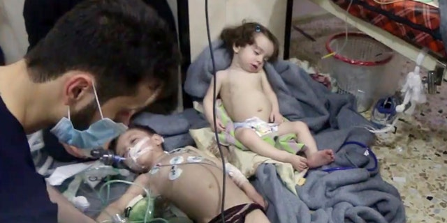This image made from video released by the Syrian Civil Defense White Helmets, which has been authenticated based on its contents and other AP reporting, shows medical workers treating toddlers following an alleged poison gas attack in the opposition-held town of Douma, in eastern Ghouta, near Damascus, Syria, Sunday, April. 8, 2018.