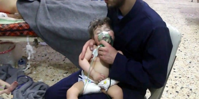 A member of the Syria Civil Defense administers oxygen to baby after suspected gas attack in Syria on April 7, 2018.