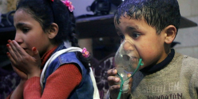This image released early Sunday, April 8, 2018 by the Syrian Civil Defense White Helmets, shows a child receiving oxygen through respirators following an alleged poison gas attack in the rebel-held town of Douma, near Damascus, Syria.