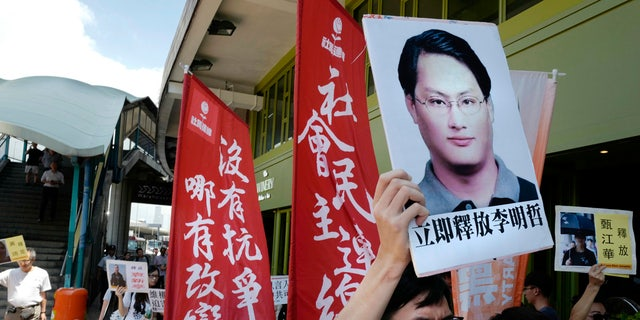 In this Sept. 11, 2017, file photo, a protester raises a picture of Taiwanese activist Lee Ming-che during a demonstration outside the Chinese liaison office in Hong Kong.
