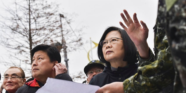 In this photo released by the Taiwan Presidential Office, Taiwan's President Tsai Ing-wen, center, is briefed at the site of a collapsed building from an earthquake.
