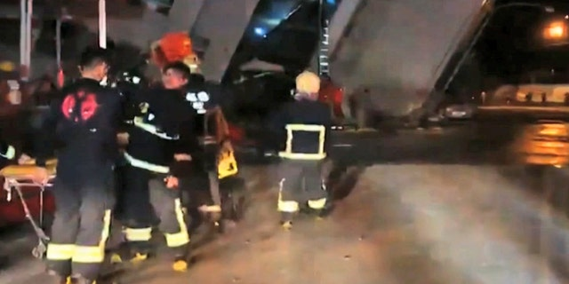 In this image from TV, emergency services attend after a building collapsed on its side, as a man climbs a ladder to gain access to the building, center background, after an early morning earthquake in Hualien County, eastern Taiwan.