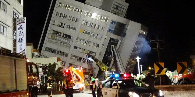 Rescuers are seen entering a building that collapsed onto its side from an early morning 6.4 magnitude earthquake in Hualien County, eastern Taiwan.