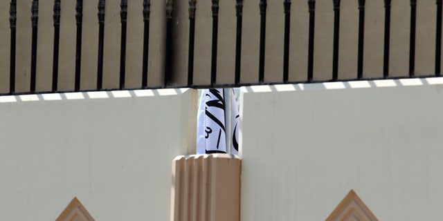 This photo taken on Thursday, June 20, 2013 shows the Taliban flag visible through a gap in a wall of the new office of the Afghan Taliban in Doha, Qatar after the opening of the office.