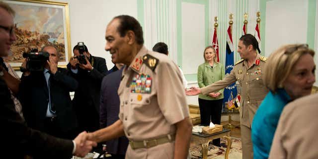 July 15, 2012: US Secretary of State Hillary Rodham Clinton, back center, watches as Field Marshal Hussein Tantawi, second left, greets members of the American delegation before a meeting at the Ministry of Defense in Cairo, Egypt.