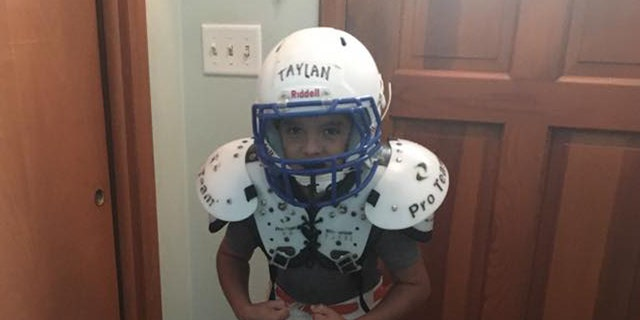 Taylan flexes his muscles in his football gear.