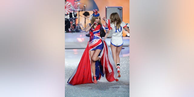 Singer Taylor Swift performs as model Cara Delevingne (R) presents a creation during the annual Victoria's Secret Fashion Show in New York, November 13, 2013. REUTERS/Lucas Jackson (UNITED STATES - Tags: ENTERTAINMENT FASHION) - RTX15CKZ