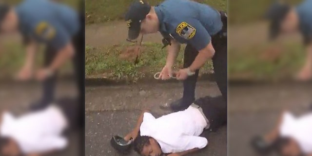 Image from bodycam video showing Timmy Patmon, 23, being handcuffed after being struck by a patrol car driven by Officer Taylor Saulters in east Athens, Georgia.