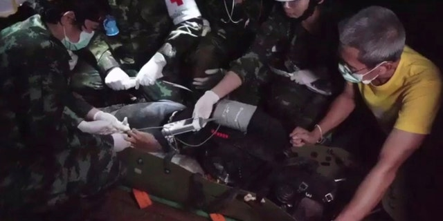 This undated photo from video released via the Thai NavySEAL Facebook Page on Wednesday, July 11, 2018, shows rescuers hold an evacuated boy inside the Tham Luang Nang Non cave in Mae Sai, Chiang Rai province, in northern Thailand.