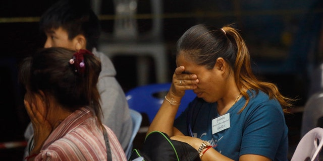 Family members react after hearing the news that the missing 12 boys and their soccer coach have been found, in Mae Sai, Chiang Rai province, in northern Thailand.