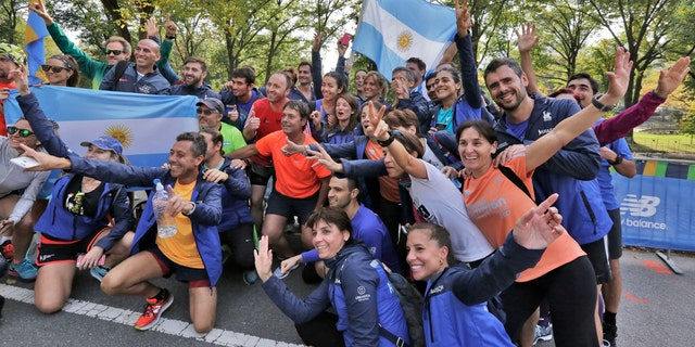 A group of runners from Argentina pose for photos with their country's flag, near the finish of the New York City Marathon, in New York's Central Park, Friday, Nov. 3, 2017.