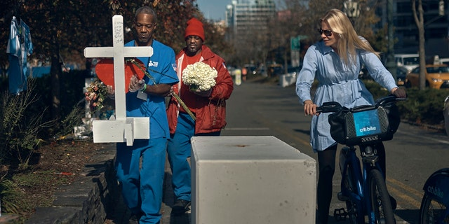 A biker watches as workers carry a cross to a memorial for the victims of Tuesday's truck attack on Friday, Nov. 3, 2017, in New York.