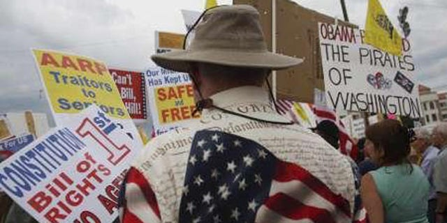 """In this Aug. 31 file photo, """"tea party"""" demonstrators hold signs at a protest in Flagstaff, Ariz. (Reuters Photo)"""