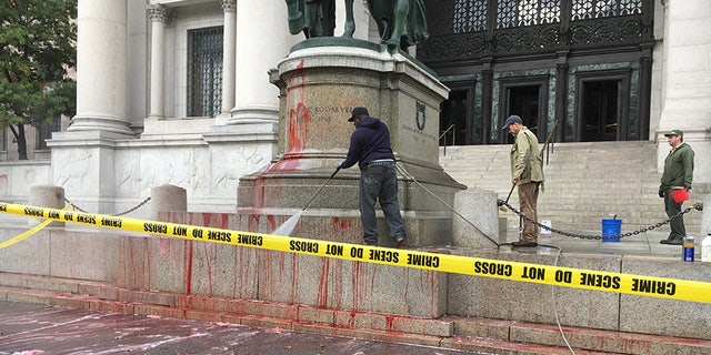 Workers with the New York City Department of Parks and Recreation clean up the Theodore Roosevelt statue.
