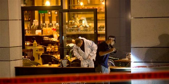 Agentes de la policía de Israel examinan la escena de una balacera en Tel Aviv, Israel, el 8 de junio de 2016. Dos pistoleros palestinos abrieron fuego en el centro de Tel Aviv el miércoles por la noche, matando a tres personas e hiriendo a al menos cinco más, segun la policía de Israel. (AP Foto/Sebastian Scheiner)