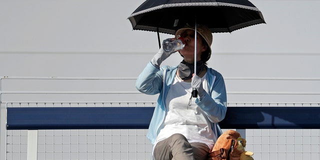 A fan shelters under an umbrella and sips a drink as she watches the match between Fabio Fognini, of Italy, and Michael Mmoh during the first round of the U.S. Open tennis tournament