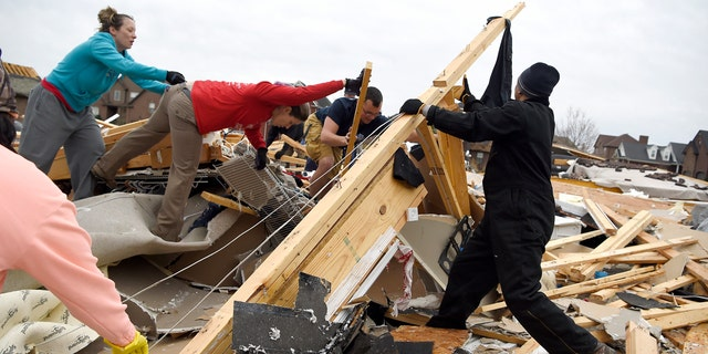 Neighbors help collect clothing and look for pets at a destroyed home Sunday morning after a fierce storm hit Saturday, Feb. 24, 2018, in the Farmington subdivision in Clarksville, Tenn.