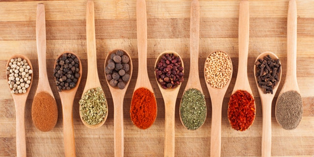 various spices on wooden spoons on cutting board
