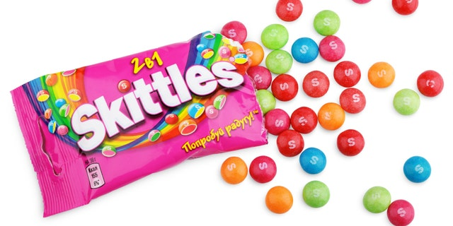 Closeup of unwrapped Skittles candy made by Wm. Wrigley Jr. Company isolated on white background with clipping path