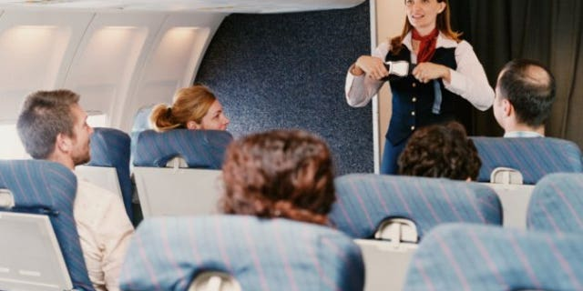 Female Flight Attendant Demonstrating Safety Procedures to Passengers on a Plane
