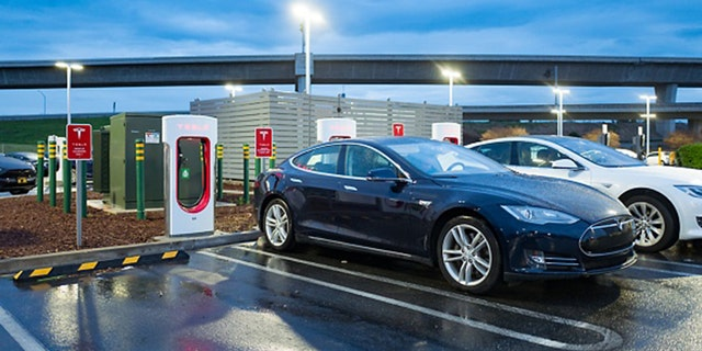 At dusk, Tesla Motors electric cars are plugged in and charging at a Tesla Supercharger electric vehicle charger in Pleasanton, California, March 12, 2018. (Photo by Smith Collection/Gado/Getty Images)