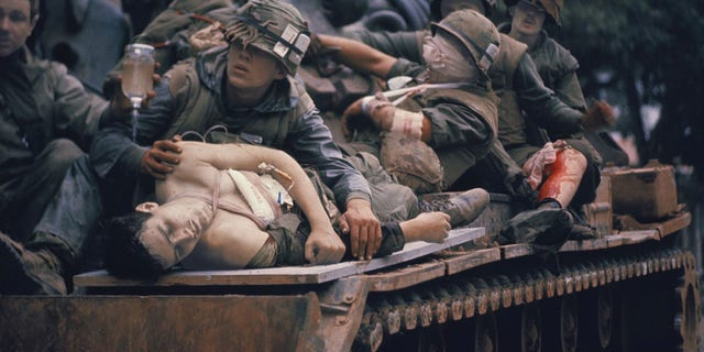 The war photographers most famous picture – The Tank – captures a young American soldier who had been shot through the chest laying over a door, used as a stretcher, on top of a tank, while his fellow marines are assisting him and trying to get him to a safe haven.