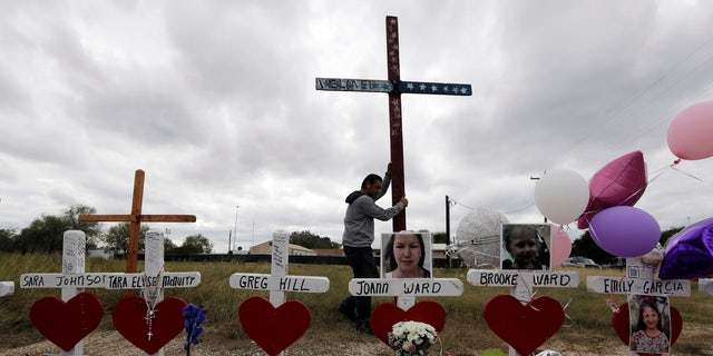 Miguel Zamora strands a cross for the victims of the Sutherland Springs First Baptist Church shooting at a makeshift memorial, Nov. 11, 2017.
