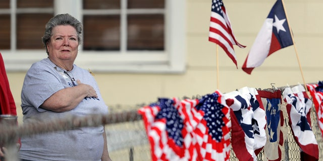 Donna King stands for the national anthem during a Veterans Day event, Saturday, Nov. 11, 2017, in Sutherland Springs, Texas.